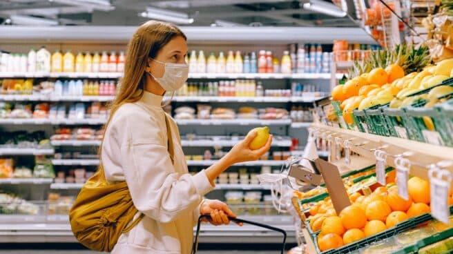 Una mujer con mascarilla sostiene una limón en un supermercado
