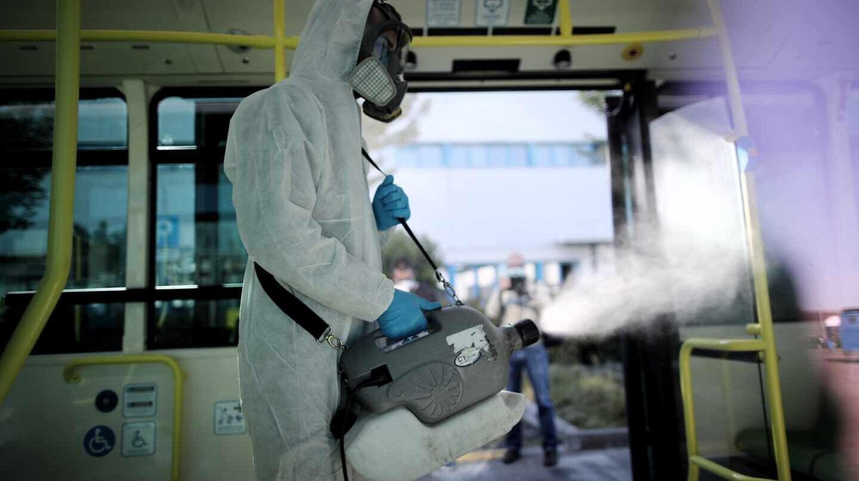 Un operario de la EMT desinfecta con un nebulizador un autobús de línea, en Madrid.