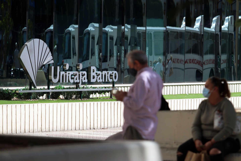 Dos personas en las inmediaciones de la sede de Unicaja Banco en Málaga.