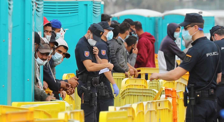 Policías nacionales y migrantes, en el muelle grancanario de Arguineguín.