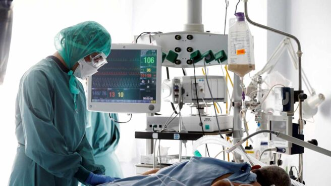 Un profesional sanitario, atendiendo a un enfermo de coronavirus en la UCI de un hopital.