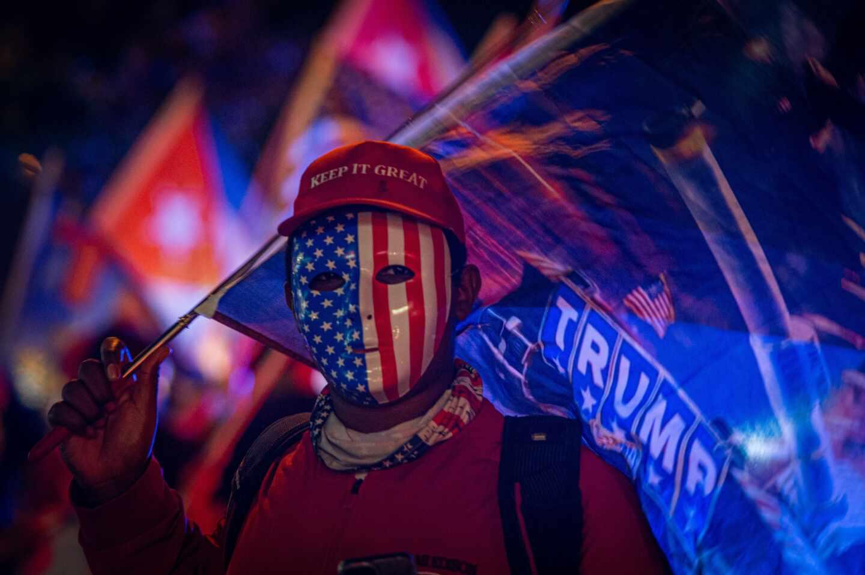 """Un simpatizante de Donald Trump viste careta con la bandera estadounidense y una gorra que dice """"Mantén (América) grandiosa"""" mientras espera los resultados de las elecciones presidenciales en Miami"""
