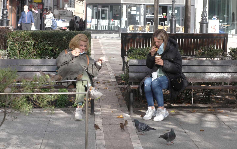Dos mujeres toman café en una plaza de Gijón.