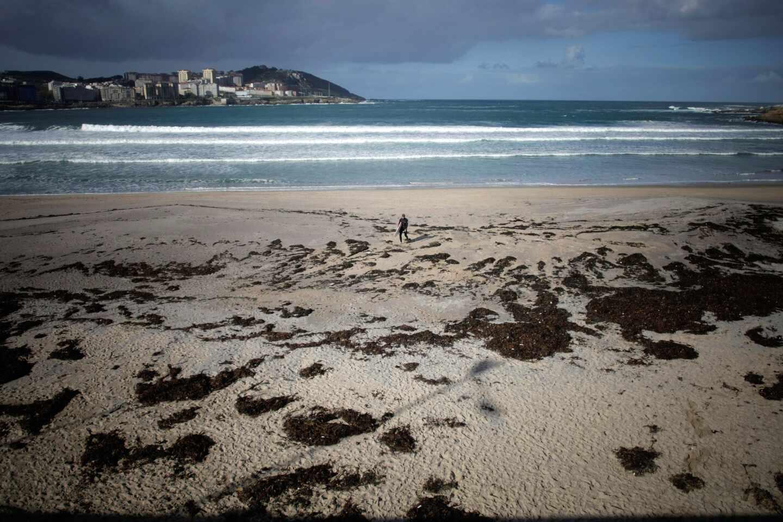 Un surfista camina por la playa del Orzán de A Coruña.