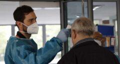 Personal sanitario toma la temperatura a una persona en la entrada de un centro de mayores en Madrid.