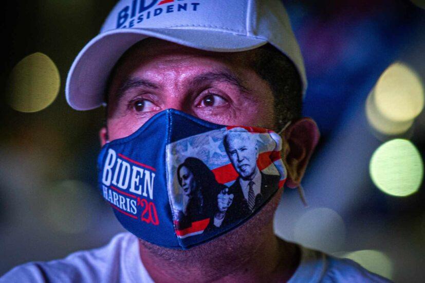 Un latino sigue el recuento de la votación con una mascarilla de Joe Biden y Kamala Harris en Miami