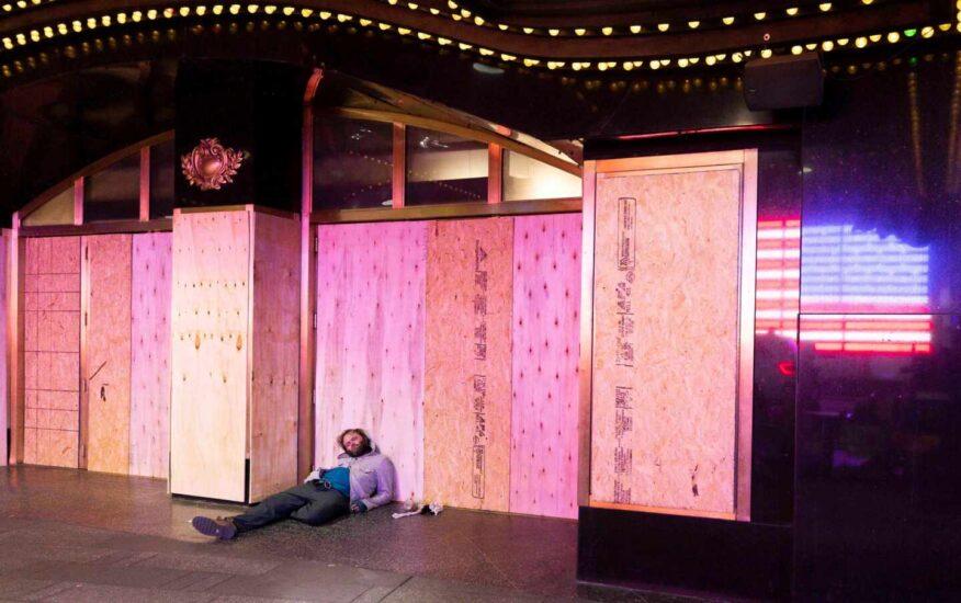 Un hombre duerme apoyado en un panel de madera colocado en el escaparate de una tienda en Nueva York para prevenir disturbios
