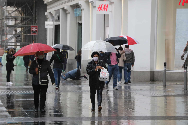 Transeúntes caminan por el centro de la capital protegiéndose de la lluvia.