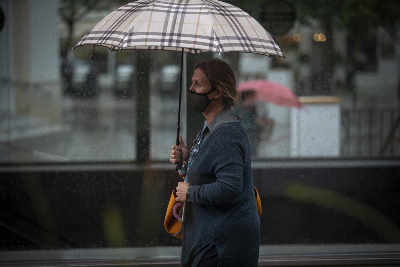 Una mujer se protege bajo su paraguas. EP.
