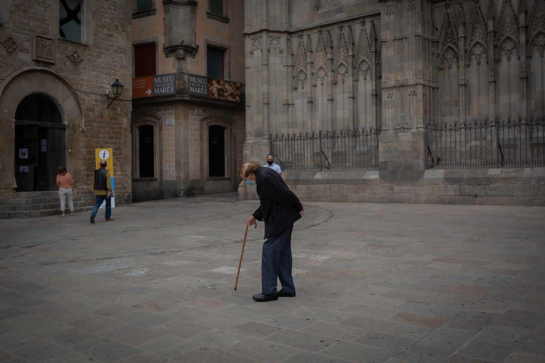 Un anciano camina por una plaza del Barrio Gótico de Barcelona.