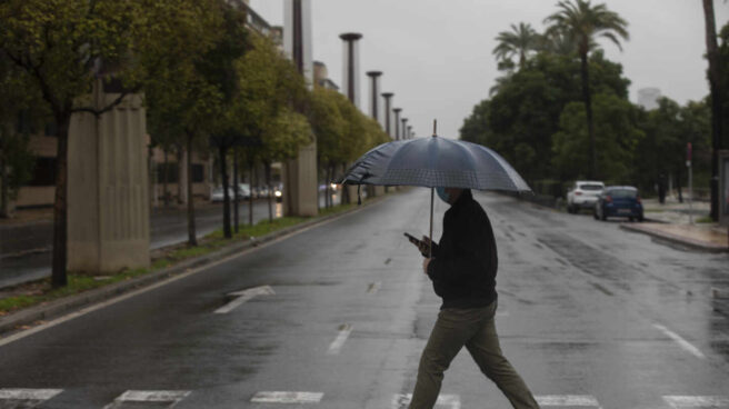 Un hombre camina protegido de la lluvia con un paraguas.