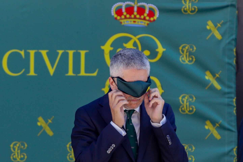 El ministro Grande-Marlaska se coloca la mascarilla en un acto oficial de la Guardia Civil.