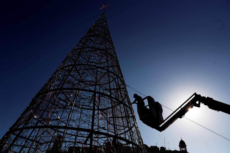 Un operario trabaja en el montaje del árbol de navidad de la plaza del Ayuntamiento de Valencia.