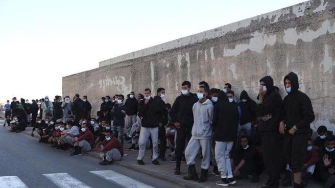 Un grupo de inmigrantes tras ser desalojado del muelle de Arguineguín.