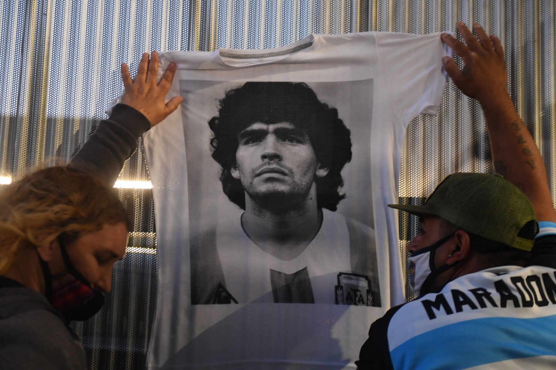 Hinchas cuelgan camisetas conmemorativas de Maradona en el hospital donde fue operado a principios de noviembre.
