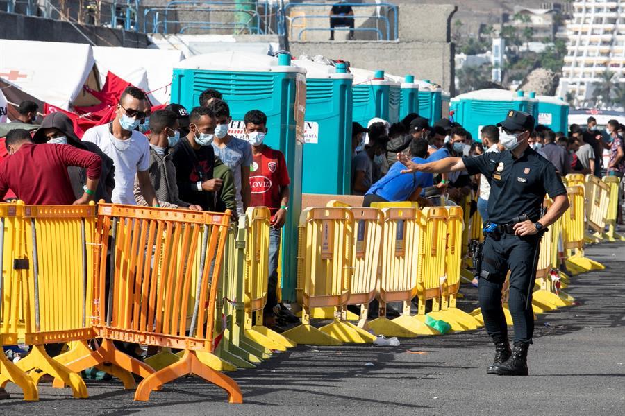 Un policía nacional se dirige a un grupo de inmigrantes en el puerto de Arguineguín.