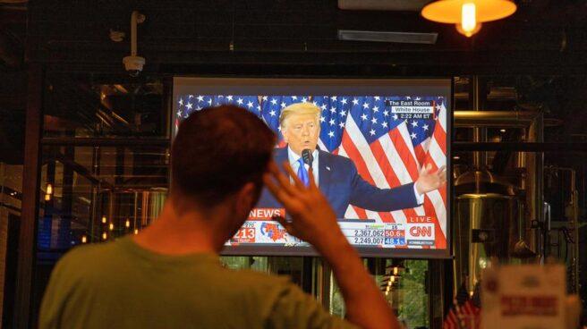 Un hombre ve por televisión al presidente Donald Trump durante la noche electoral.