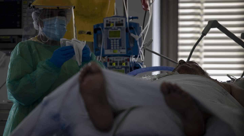 Un sanitario atiende a un paciente en la UCI del Hospital Ramón y Cajal, en Madrid.