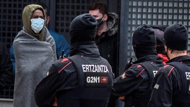 Un asistente a la fiesta (izq) aguarda junto a agentes de la Ertzaintza este lunes durante el proceso de identificación de los 67 asistentes a una fiesta celebrada la pasada en la hospedería de un convento de Derio (Bizkaia).