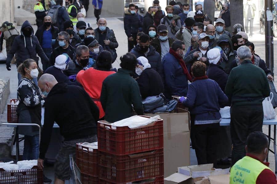Decenas de personas hacen cola para recibir ayuda en un centro social religioso de Barcelona.