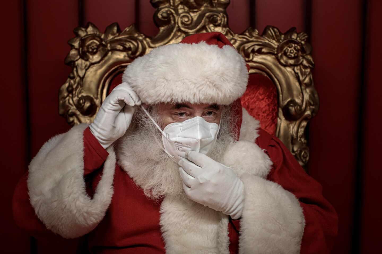 Un Papá Noel se pone la mascarilla en un centro comercial de Valencia.