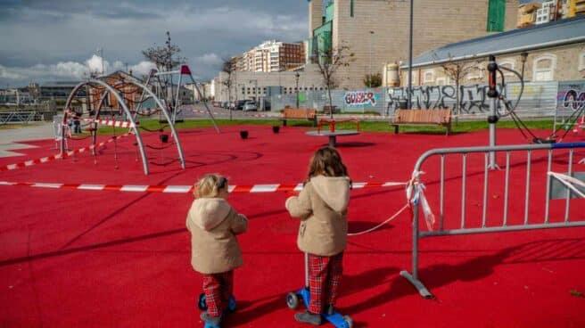 Dos niñas observan un parque cerrado de Santander.