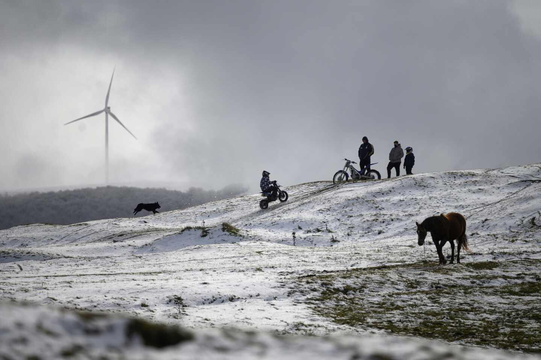 Varias personas transitan por un paraje nevado en la localidad cántabra de Requejo, en un fin de semana marcado por las bajas temperaturas en el norte peninsular.