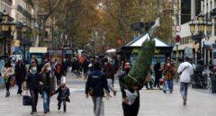Una persona transporta un árbol de navidad por las Ramblas de Barcelona.