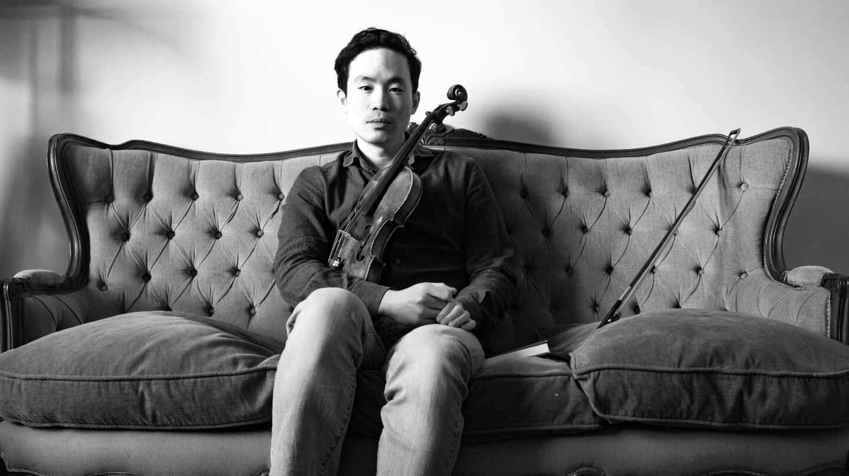 Aaron Lee, en el sofá de su salón con su violín