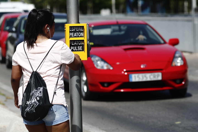 Una chica se dispone a cruzar la calle, en Madrid.