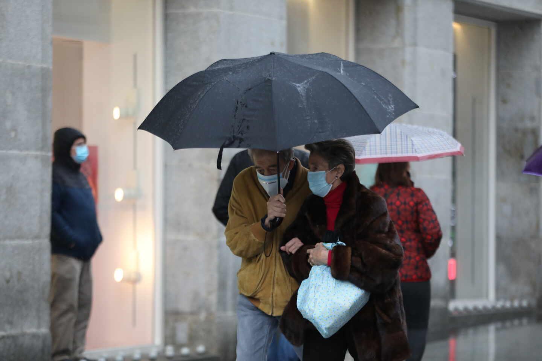 Dos personas pasean protegidas con paraguas por el centro de la capital, en Madrid.