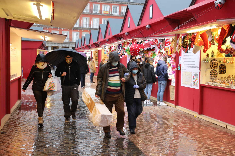Personas protegidas por paraguas caminan por el mercadillo navideño de la Plaza Mayor, en Madrid.