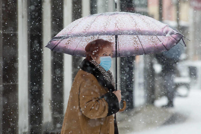 Una mujer se cubre de la nieve con un paraguas en Becerrea, en Lugo.