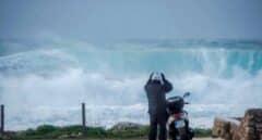 Un motorista se prepara para montar en su scooter mientras grandes olas rompen en Binianolla (Menorca).