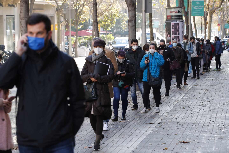 Multitud de personas hacen cola para hacerse test de antígenos en un laboratorio privado de Barcelona.