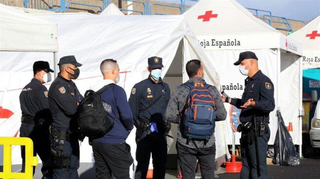 Policías junto a inmigrantes magrebíes en el muelle de Arguineguín.