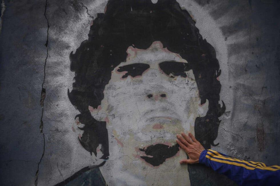 Un fan de Boca Juniors toca un mural de Diego Armando Maradona.