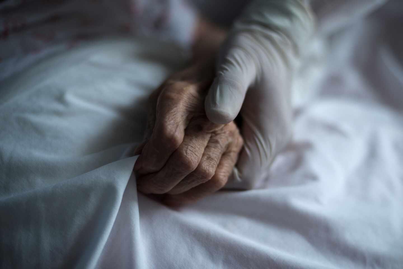 Una trabajadora de una residencia sujeta la mano de una anciana.
