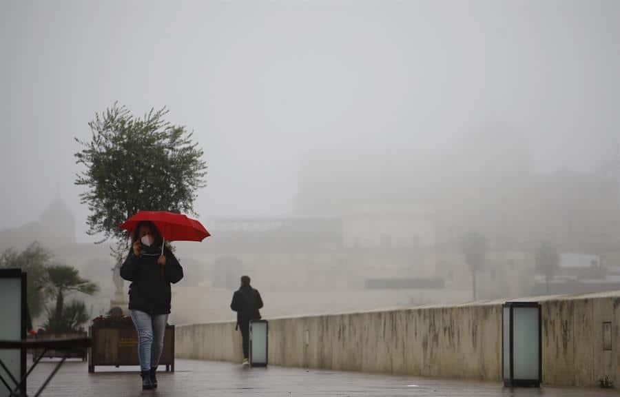 Una mujer camina por el Puente Romano de Córdoba.