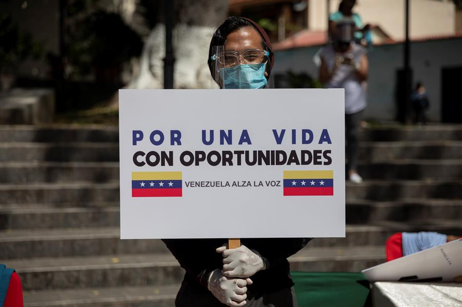 Un hombre sujeta un cartel con el lema 'Venezuela alza la voz'