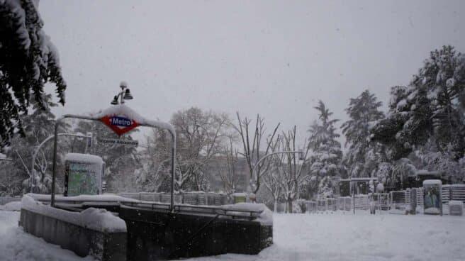 Entrada a la estación de metro Vicente Aleixandre cubierta de nieve en Madrid.