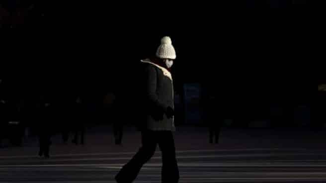 Una mujer con mascarilla camina por una calle de Valencia.