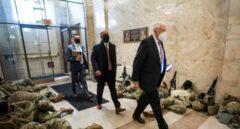 El líder de la mayoría, Steny Hoyer, pasa junto a miembros de la Guardia Nacional que intentan dormir dentro del Capitolio.
