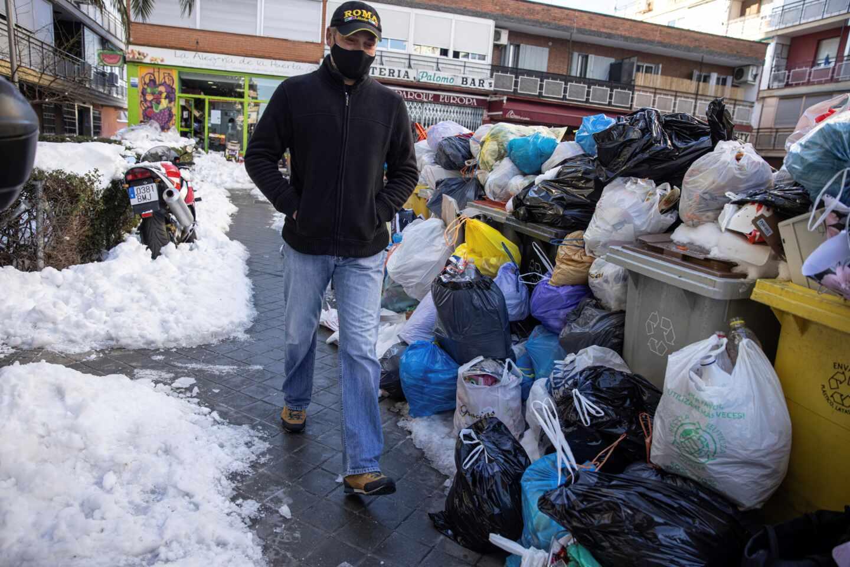 Un hombre camina junto a las bolsas de basura que se acumulan en las aceras y en los cubos situados en las calles de Madrid.