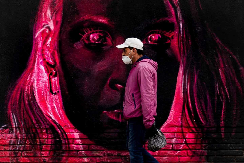 Una persona pasa frente a un grafitti este lunes en Barcelona