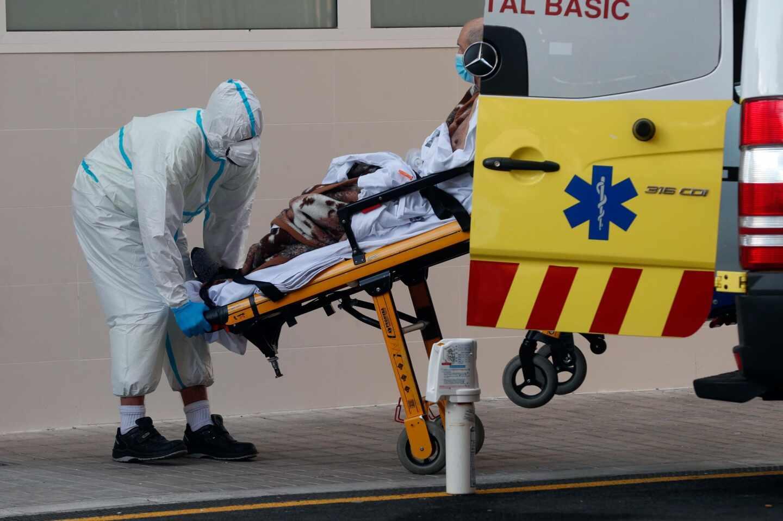 Un sanitario traslada a un enfermo en el Hospital Clínico de Valencia.