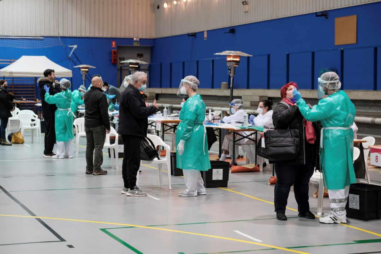 Varias personas se someten a una prueba de antígenos durante el cribado masivo para detectar casos covid-19 en un polideportivo.