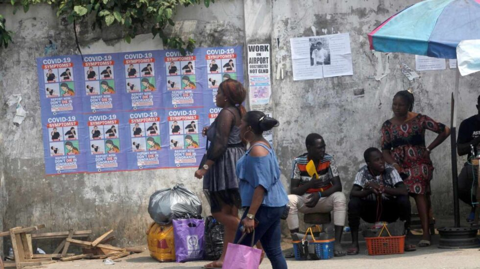 Varias personas caminan por Lagos (Nigeria), ante varios carteles que alertan de los síntomas del coronavirus