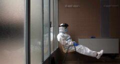 Una profesional sanitaria descansa tras varias horas realizando pruebas PCR.