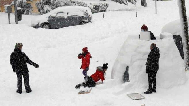 Varias personas construyen un iglú en una calle de Madrid.